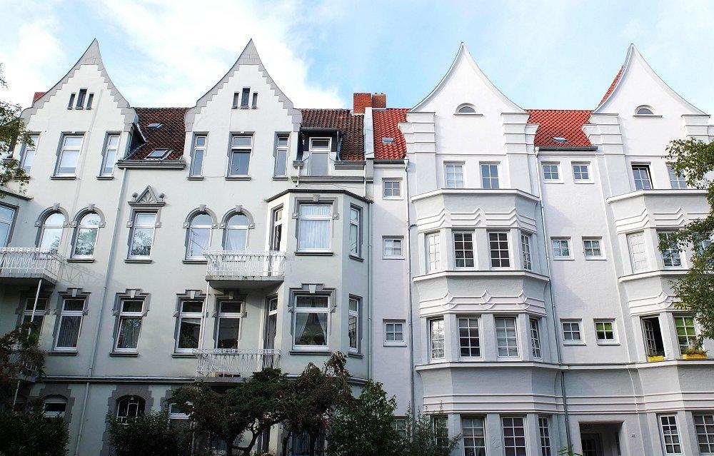 Zu sehen ist eine Frontalaufnahme einer strahlend weißen Häuserfassade.