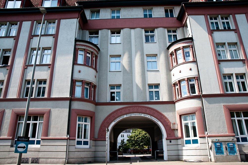 Zu sehen ist der Brüggemannhof. Eine weiß-rote Häuserfassade mit einem mittigen großen, halbrunden Bogen.