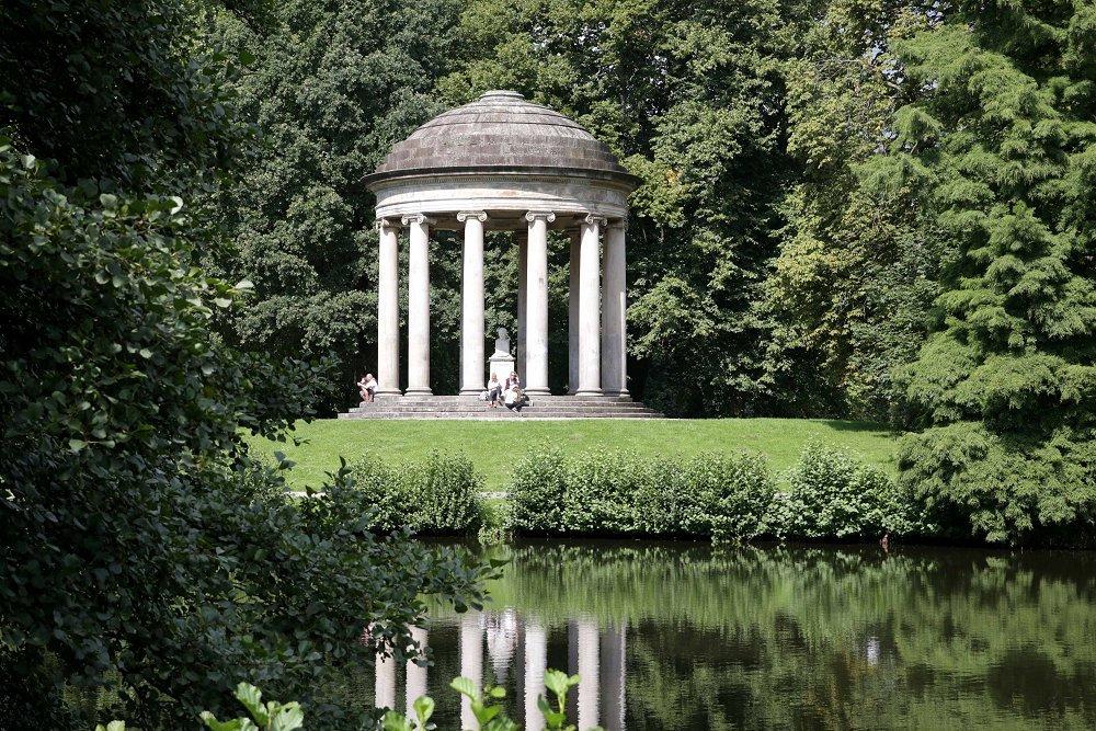 Zu sehen ist der Leibniz-Tempel. Im Hintergrund sind Bäume, im Vordergrund Wasser zu sehen.