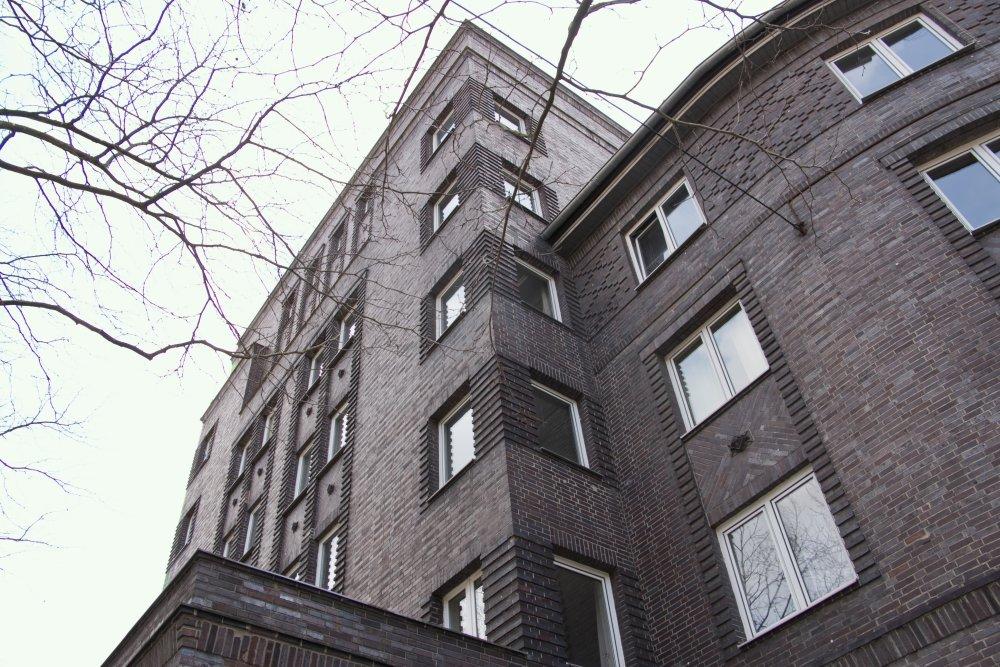 Zu sehen ist eine rot-braune Häuserfassade.