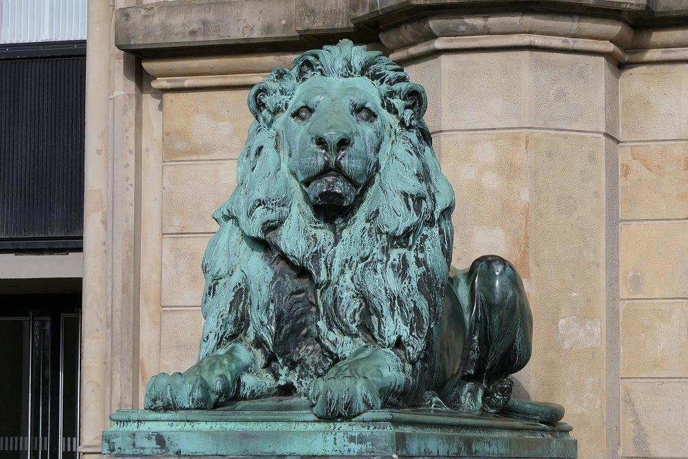 Zu sehen ist ein grüner Löwe aus Kupfer, der vor der Leibniz-Uni trohnt.