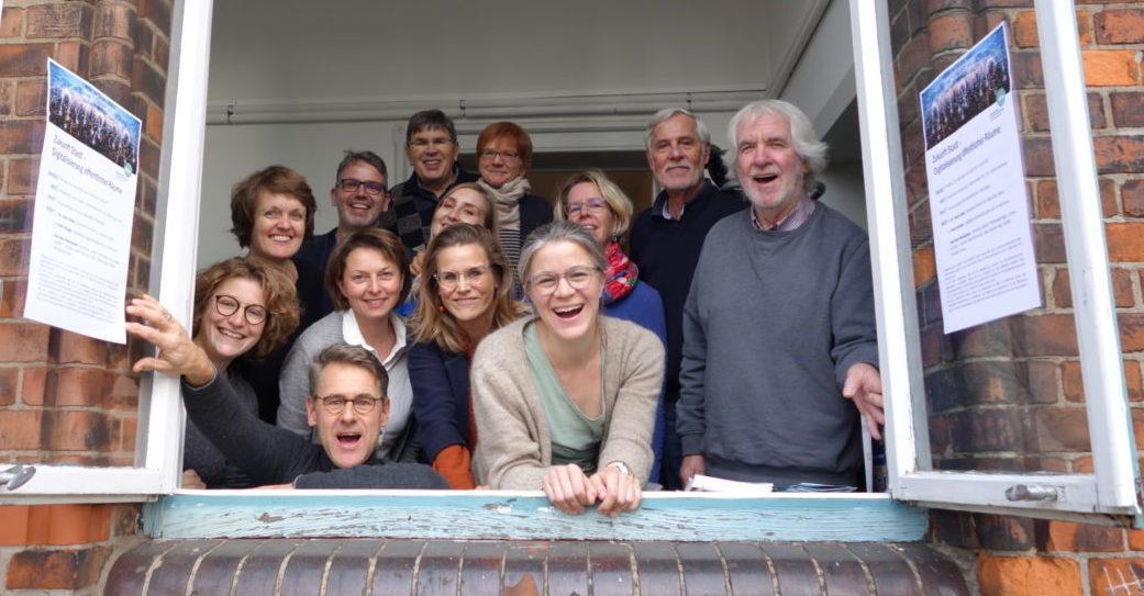 Das Team des Bürgerbüro Stadtentwicklung schaut lachend aus einem Fenster heraus.