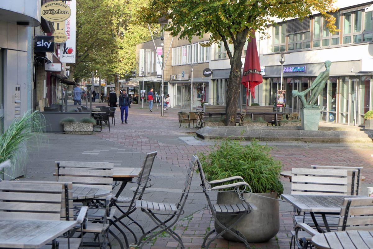 Zu sehen ist eine Fußgängerzone. Im Vordergrund stehen einige Stühle und Tische aus Holz.
