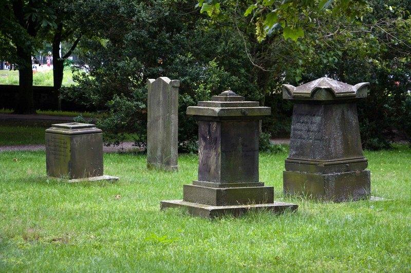 Zu sehen sind vier Grabsteine auf einem leuchtend grünen Rasen. Im Hintergrund sind Bäume und Sträucher zu sehen.