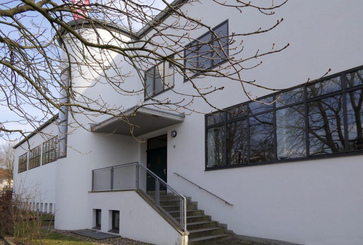 Zu sehen ist ein weißes Gebäude im Bauhaus-Stil mit einer breiten Treppe und großen Fenstern.